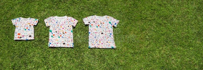 Tres camisetas que mienten en hierba verde Campamento de verano para los niños, conceptual Origen familiar grande Familia grande imagen de archivo