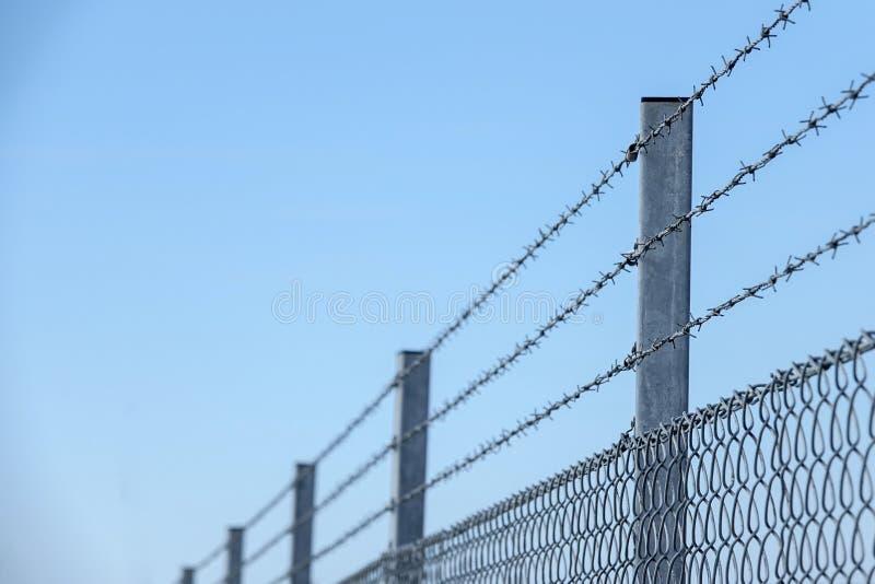 Tres capas con alambre de púas en la cima de una cerca fotografía de archivo
