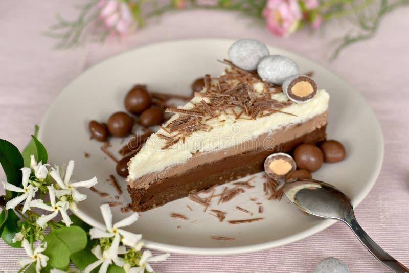 Tres capas de la torta de la crema del chocolate, rebanada en una placa fotos de archivo
