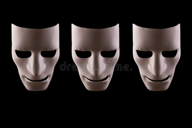 Tres caras en blanco del robot en un fondo negro fotos de archivo