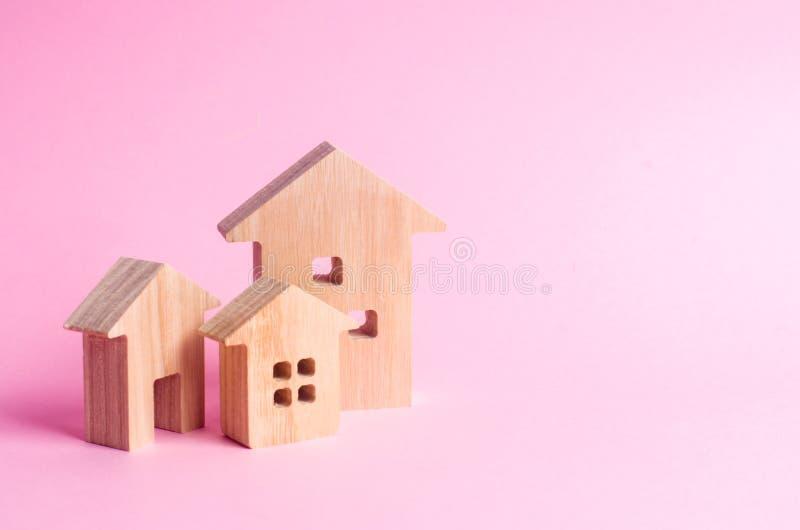 Tres casas en un fondo rosado Comprando y vendiendo de las propiedades inmobiliarias, construcción Apartamentos y apartamentos Ci foto de archivo