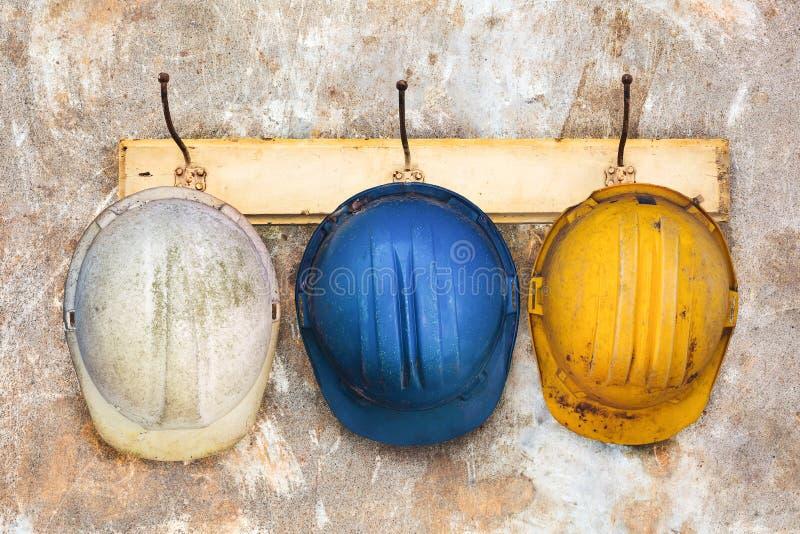 Tres cascos de la construcción que cuelgan en un perchero fotos de archivo libres de regalías