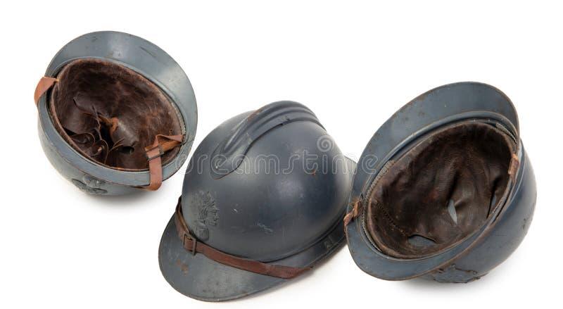 Tres cascos militares franceses de la primera guerra mundial en el fondo blanco fotos de archivo