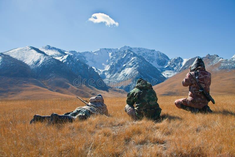 Tres cazadores que miran a través de los prismáticos en montañas de Tien Sh fotografía de archivo