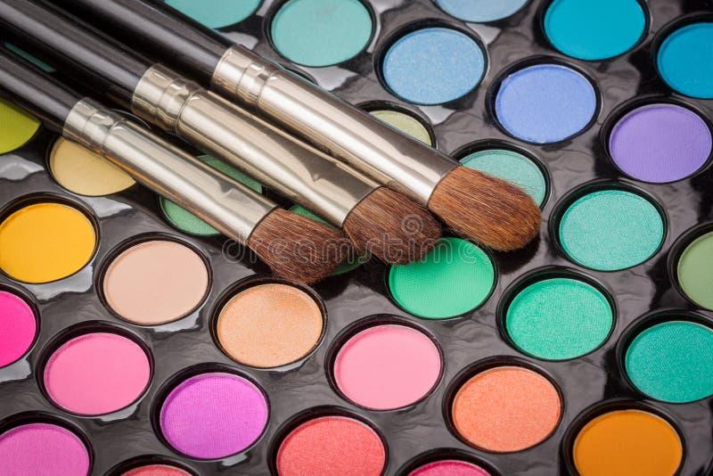 Tres cepillos del maquillaje en la paleta del maquillaje imágenes de archivo libres de regalías
