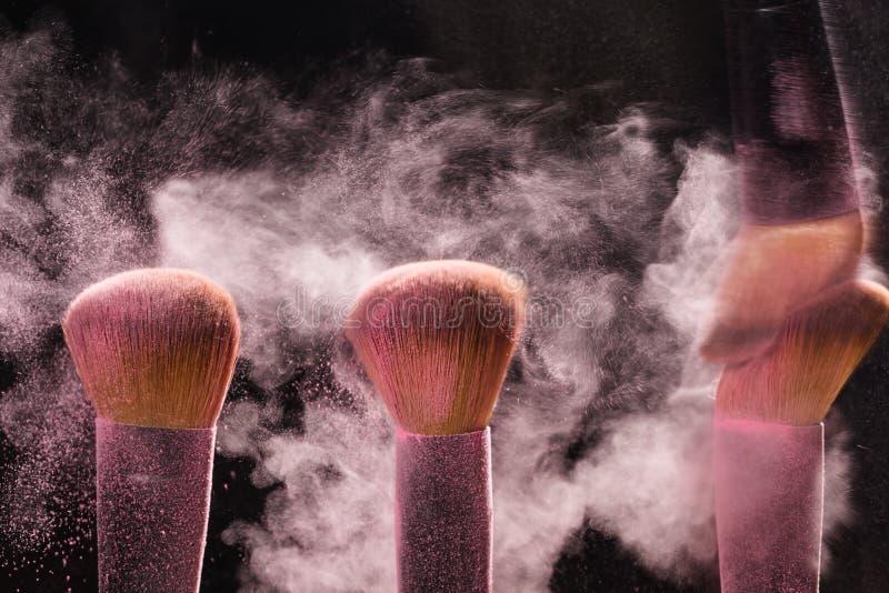 Tres cepillos para el maquillaje con el polvo mineral del maquillaje rosado en el movimiento en un fondo negro imagenes de archivo
