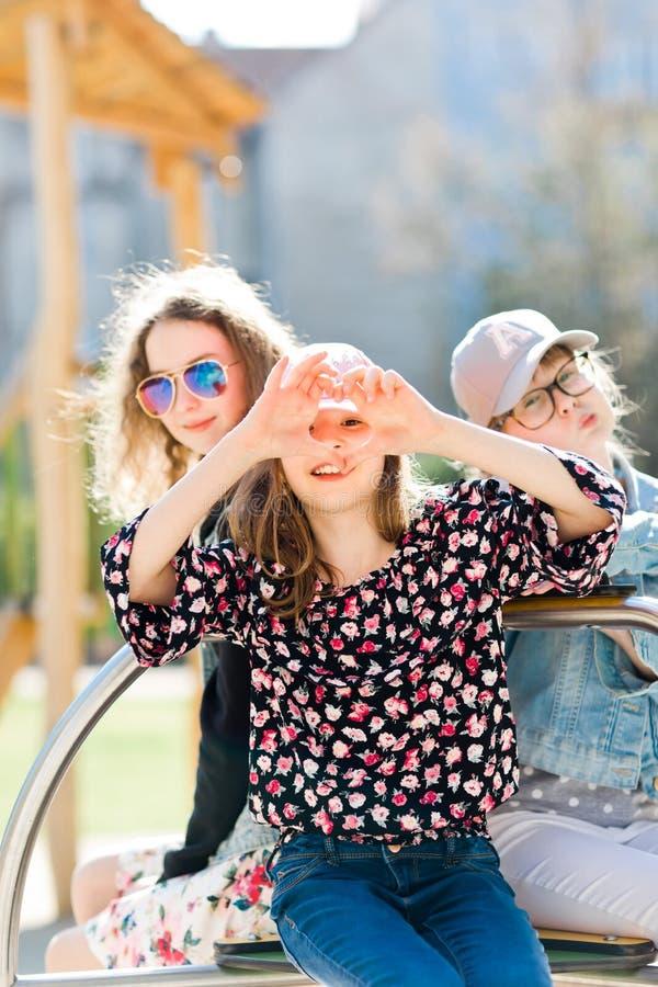 Tres chicas jóvenes en el patio que se sienta en el pequeño carrusel - oiga fotos de archivo libres de regalías