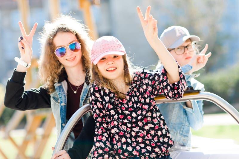 Tres chicas jóvenes en el patio que se sienta en el pequeño carrusel - vict fotos de archivo