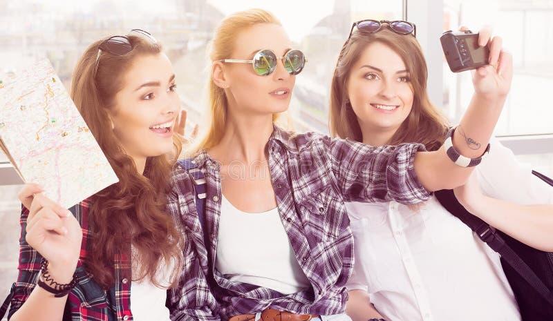 Tres chicas jóvenes en las gafas de sol que hacen el selfie en la tableta del ordenador imágenes de archivo libres de regalías