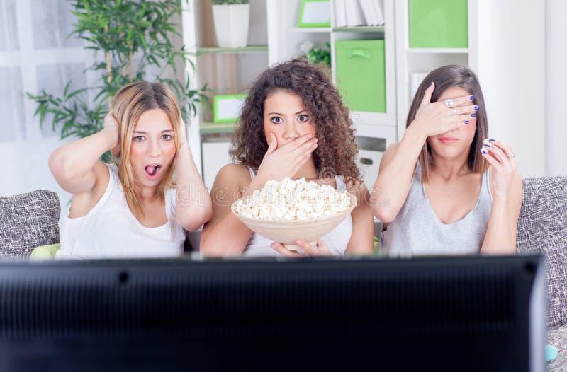Tres chicas jóvenes hermosas que miran la película triste presionada foto de archivo libre de regalías
