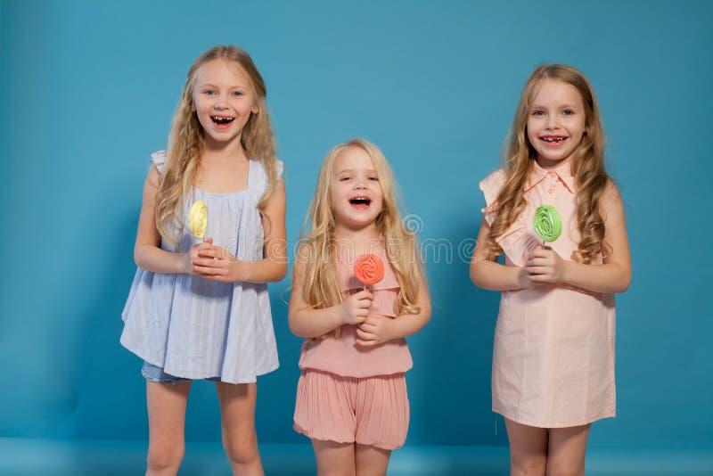 Tres chicas jóvenes hermosas y piruletas dulces del caramelo imagen de archivo