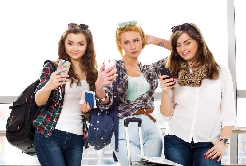 Tres chicas jóvenes que se colocan con equipaje en el aeropuerto y que miran el teléfono Un viaje con los amigos fotos de archivo