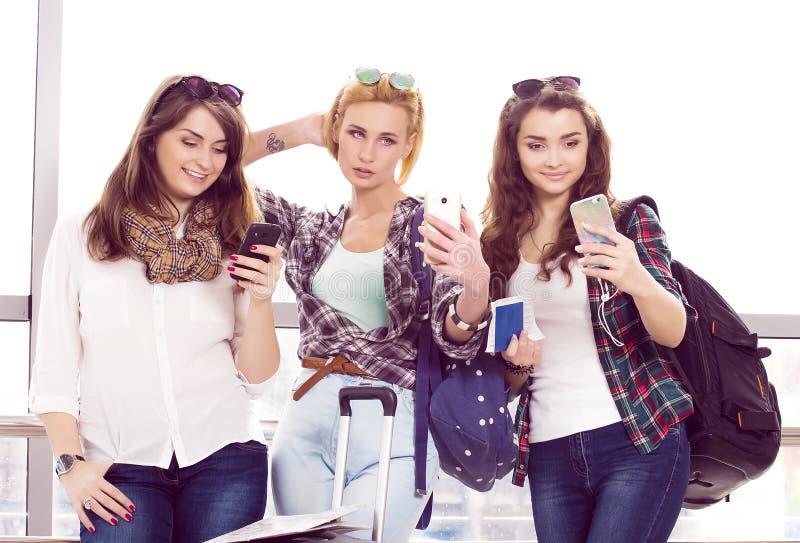 Tres chicas jóvenes que se colocan con equipaje en el aeropuerto y que miran el teléfono Un viaje con los amigos imagen de archivo libre de regalías