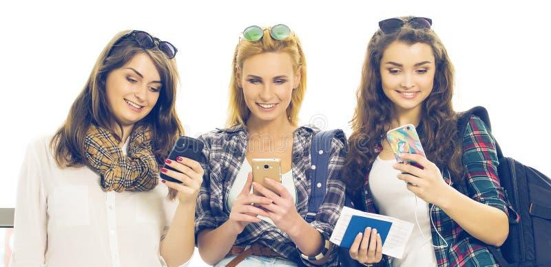 Tres chicas jóvenes que se colocan con equipaje en el aeropuerto y que miran el teléfono Un viaje con los amigos imágenes de archivo libres de regalías