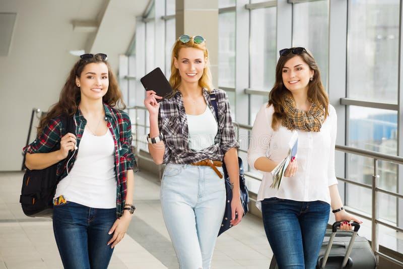 Tres chicas jóvenes van con su equipaje en el aeropuerto y ríen Un viaje con los amigos foto de archivo libre de regalías