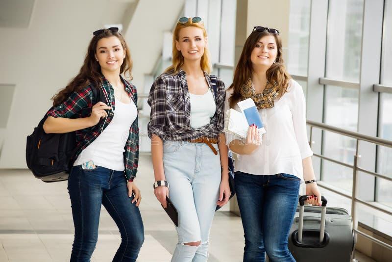 Tres chicas jóvenes van con su equipaje en el aeropuerto y ríen Un viaje con los amigos fotografía de archivo libre de regalías