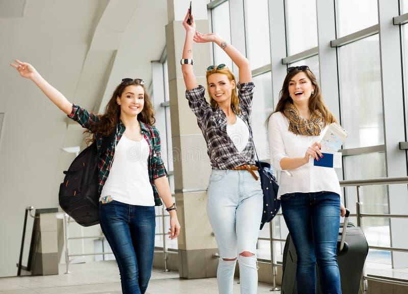 Tres chicas jóvenes van con su equipaje en el aeropuerto y ríen Un viaje con los amigos imagen de archivo libre de regalías