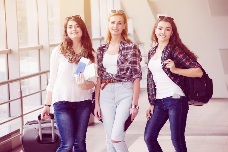 Tres chicas jóvenes van con su equipaje en el aeropuerto y ríen Un viaje con los amigos imagenes de archivo