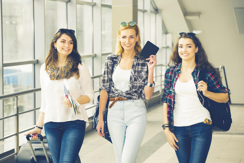 Tres chicas jóvenes van con su equipaje en el aeropuerto y ríen Un viaje con los amigos imágenes de archivo libres de regalías