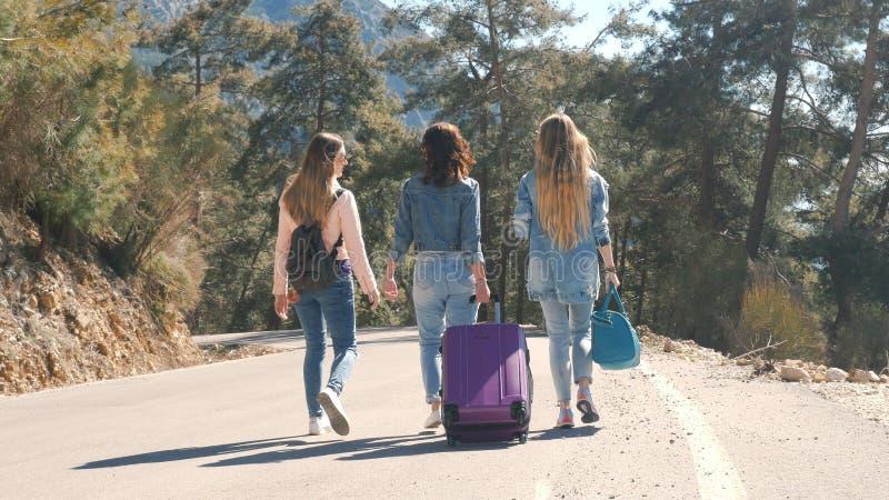 Tres chicas j?venes que caminan abajo del camino con paisaje hermoso de la naturaleza imagen de archivo libre de regalías