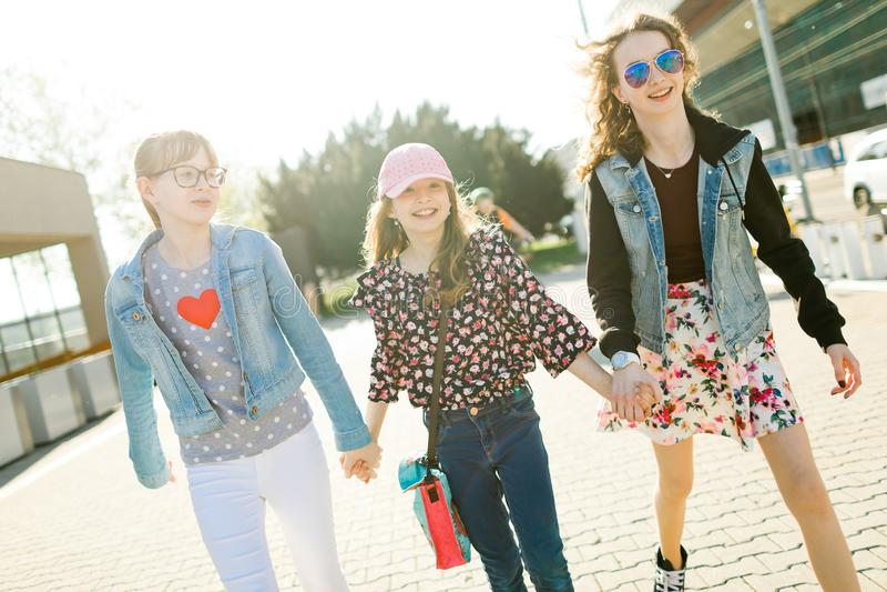 Tres chicas j?venes que caminan en las calles de la ciudad imagen de archivo libre de regalías