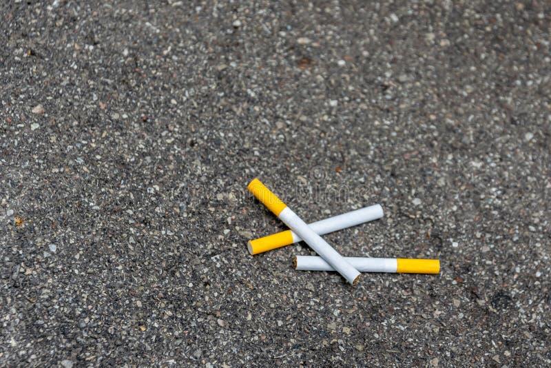 Tres cigarrillos que mienten en el pavimento fotografía de archivo libre de regalías