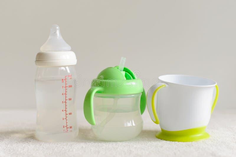 Tres clases de botellas y de tazas con agua para el bebé fotografía de archivo libre de regalías