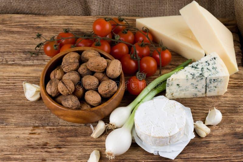 Tres clases de queso y de diversa verdura en el tablero de madera foto de archivo