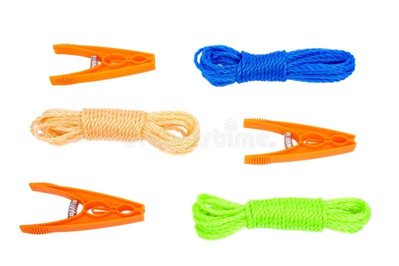 Tres clavijas anaranjadas y cuerda de tres lavaderos foto de archivo