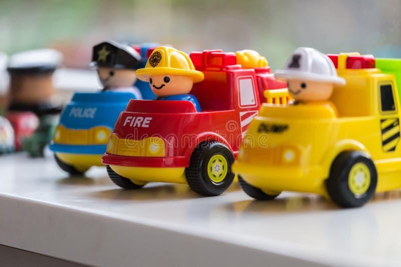 Tres coches plásticos del juguete que representan el departamento, el Departamento de Policía y la recolección de basura de bombe foto de archivo
