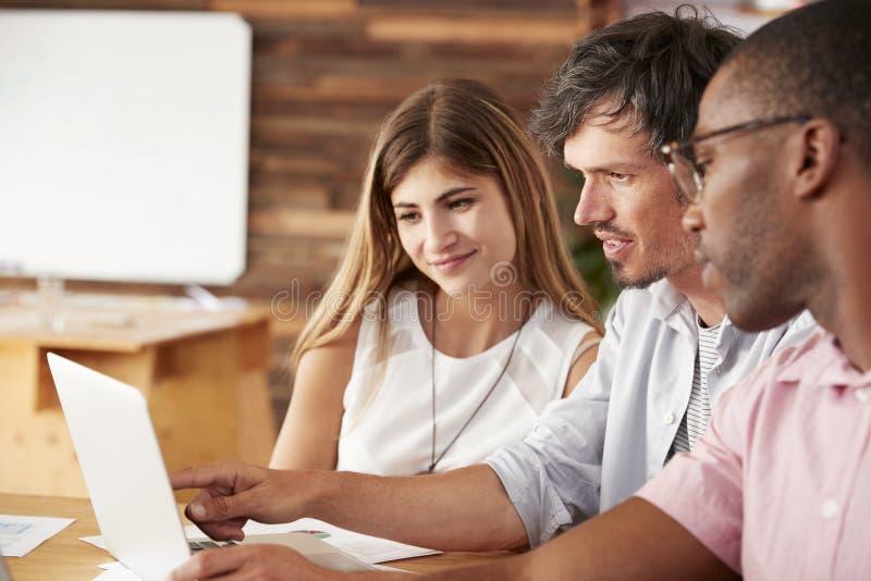Tres colegas trabajan juntos en el ordenador portátil, cierre para arriba foto de archivo libre de regalías