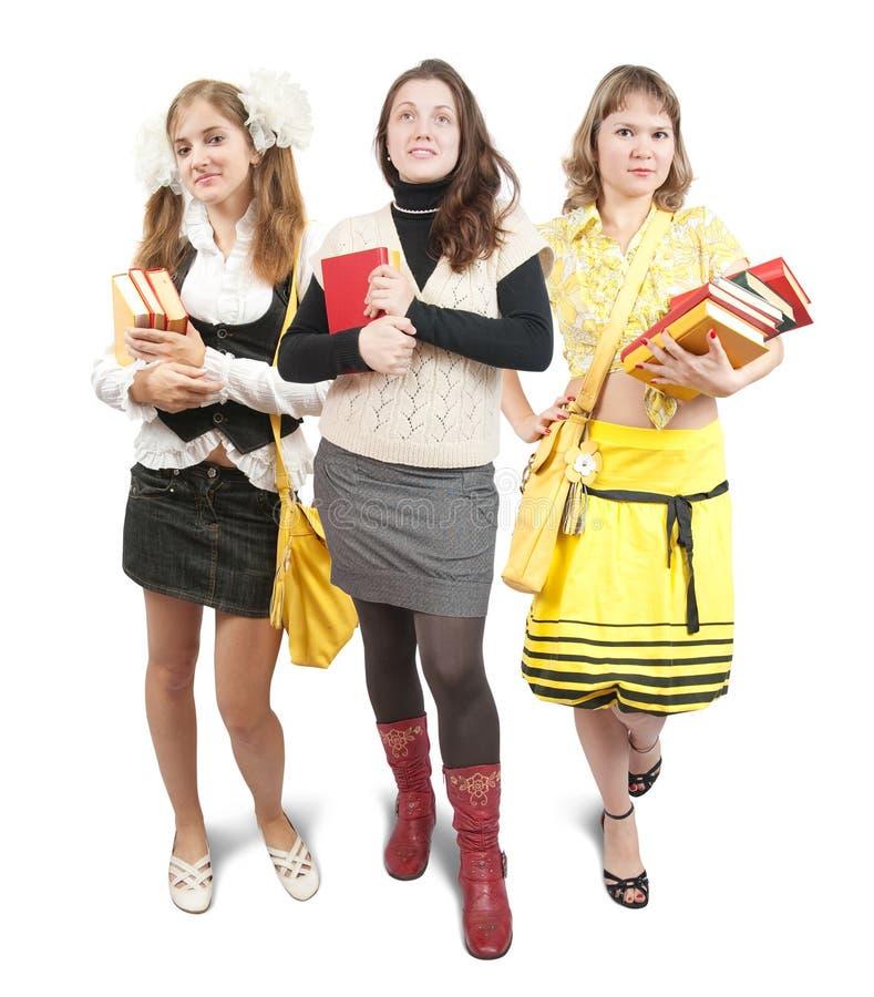Tres colegialas o estudiantes con los libros fotos de archivo libres de regalías
