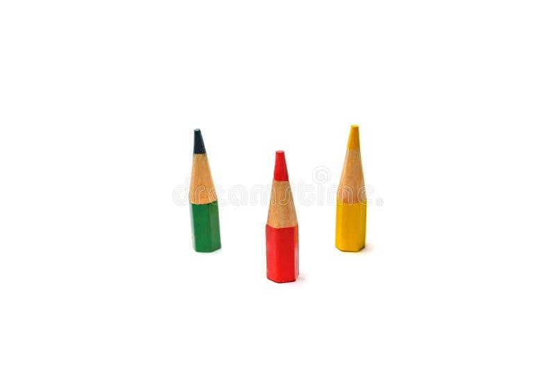 Tres colorearon los pequeños lápices mismos en un fondo blanco El concepto de uso basura-libre imagenes de archivo