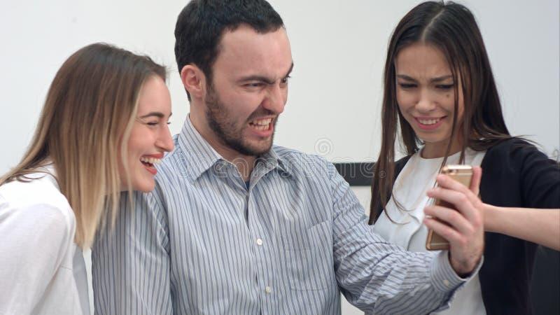 Tres compañeros de trabajo alegres que toman selfies divertidos en el teléfono fotografía de archivo libre de regalías