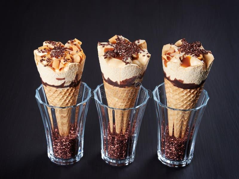 Tres conos de helado del caramelo en fondo oscuro imagenes de archivo