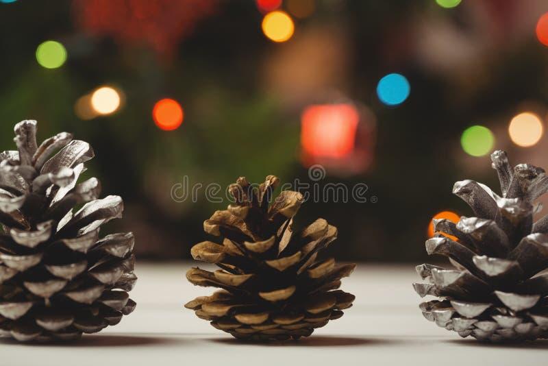 Tres conos del pino en la tabla de madera foto de archivo libre de regalías