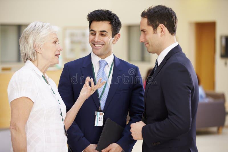 Tres consultores que se encuentran en la recepción del hospital fotos de archivo libres de regalías