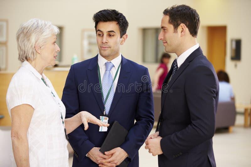 Tres consultores que se encuentran en la recepción del hospital fotografía de archivo libre de regalías