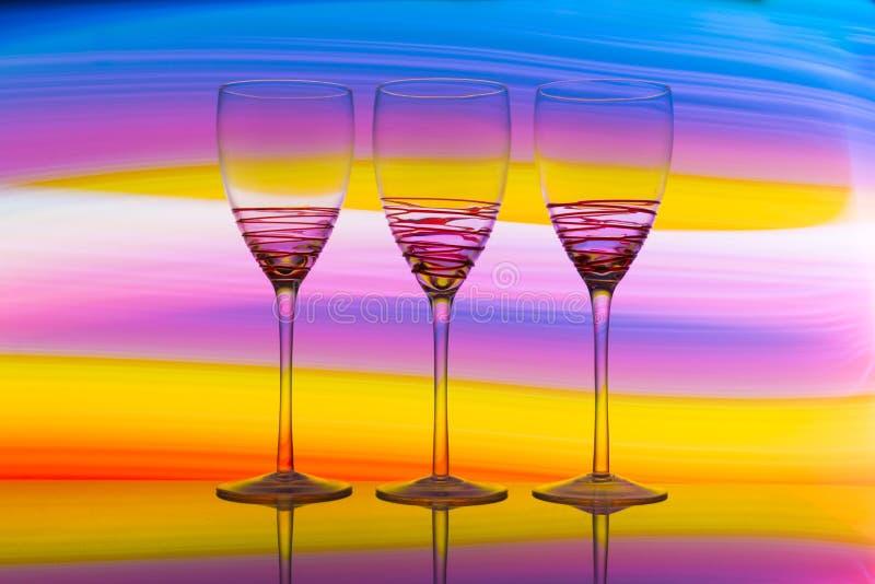 Tres copas de vino en fila con un arco iris del color detrás de ellos imagen de archivo libre de regalías