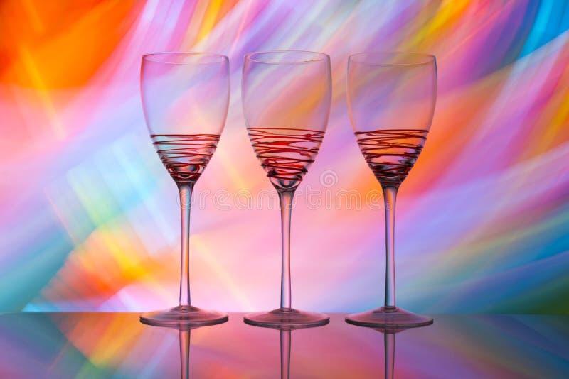 Tres copas de vino en fila con un arco iris del color detrás de ellos fotografía de archivo