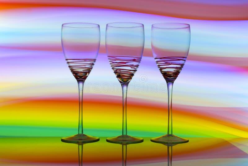 Tres copas de vino en fila con un arco iris del color detrás de ellos imagen de archivo