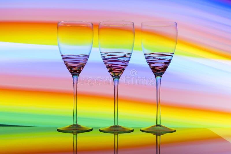 Tres copas de vino en fila con un arco iris del color detrás de ellos fotos de archivo libres de regalías