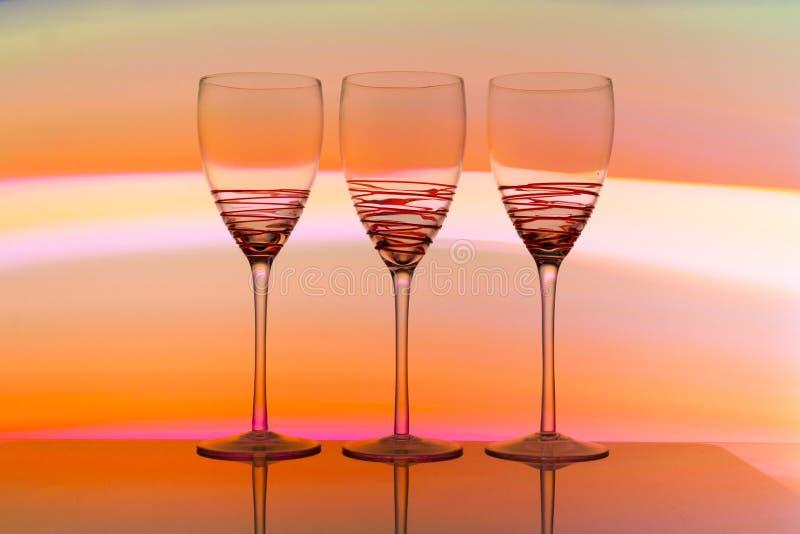 Tres copas de vino en fila con un arco iris del color detrás de ellos imagenes de archivo