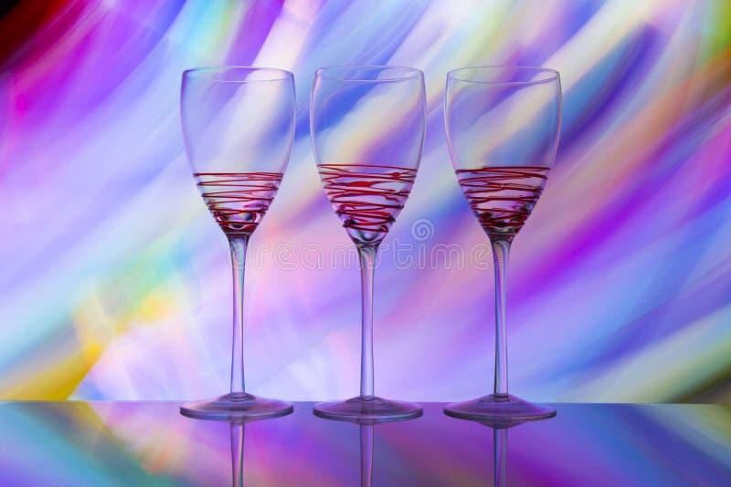 Tres copas de vino en fila con un arco iris del color detrás de ellos fotografía de archivo libre de regalías