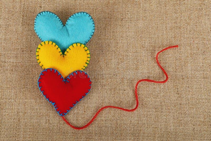 Tres corazones, amarillos, rojos y azules del arte del fieltro fotos de archivo