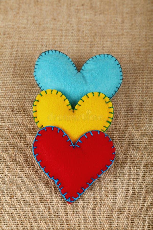 Tres corazones, amarillos, rojos y azules del arte del fieltro fotografía de archivo