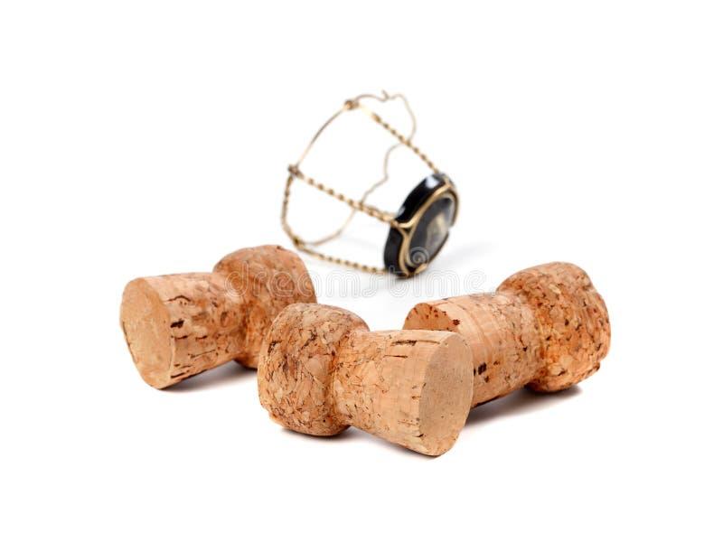 Tres corchos del vino y del muselet del champán aislados en los vagos blancos fotos de archivo