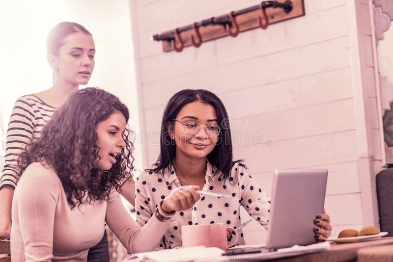 Tres creativos y estudiantes de arte inspirados que miran el vídeo educativo junto foto de archivo