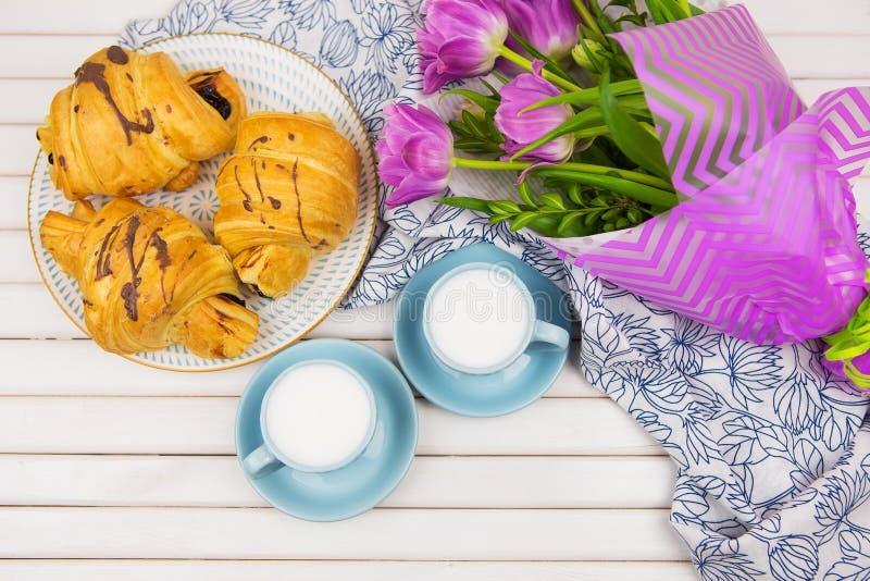 Tres cruasanes, dos tazas de caf? en la tabla y un ramo de tulipanes hermosos imagenes de archivo
