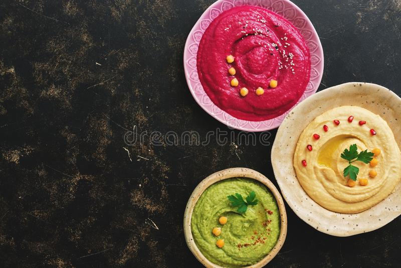 Tres cuencos con una variedad de hummus coloreado en un fondo oscuro Hummus clásico, aguacate, remolacha Visión superior, espacio foto de archivo libre de regalías